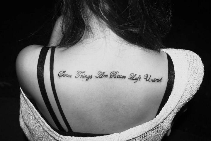 Script tattoo between shoulder blades