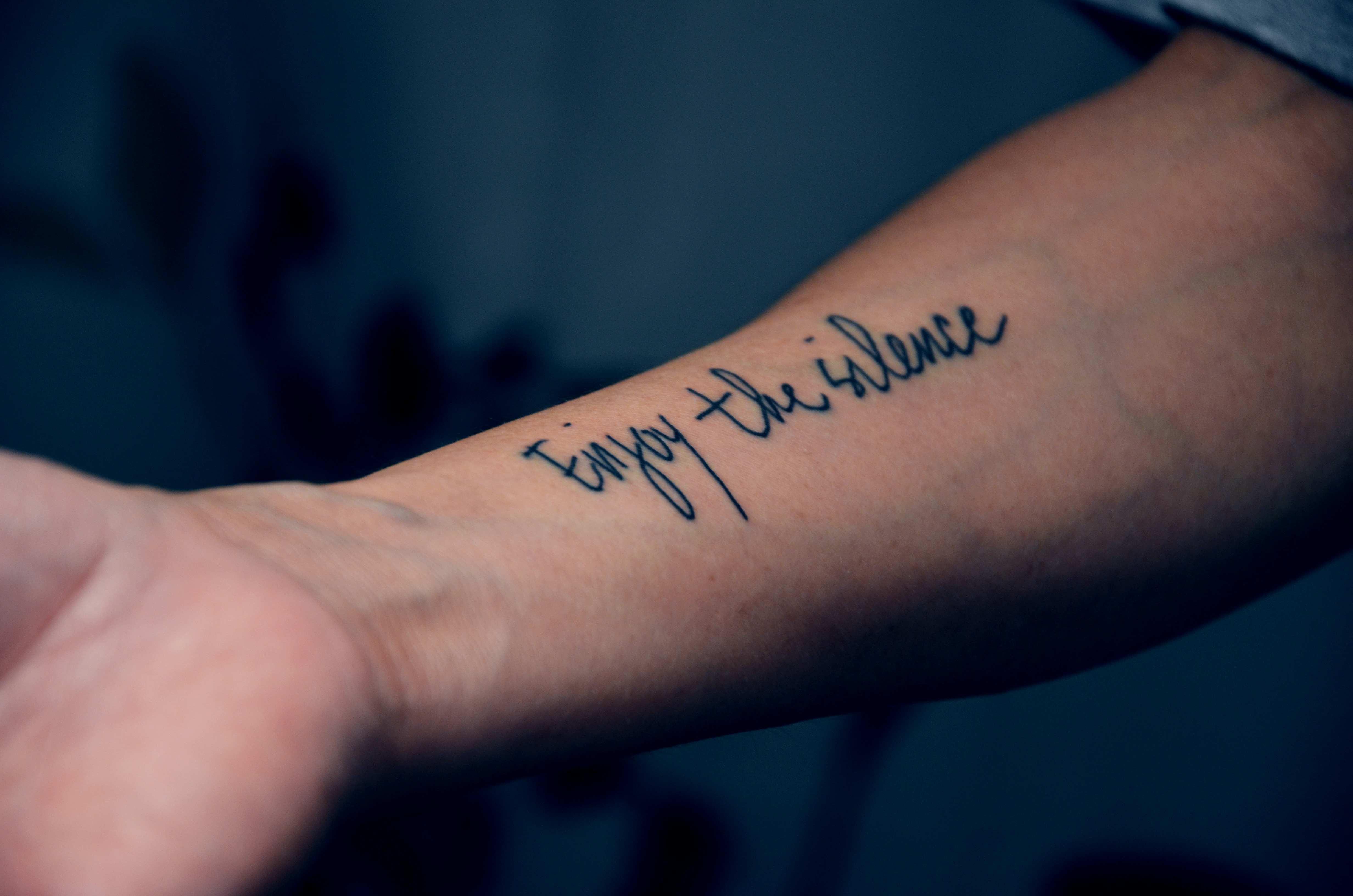 Tatuagem escrita na parte interna do braço