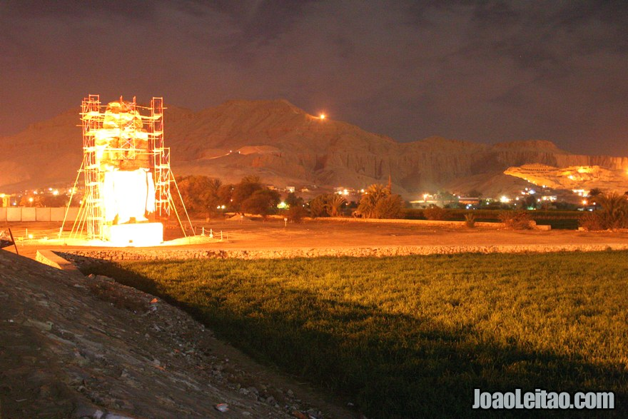 Foto de um dos Colossos de Mêmnon e do Templo de Hatshepsut à noite