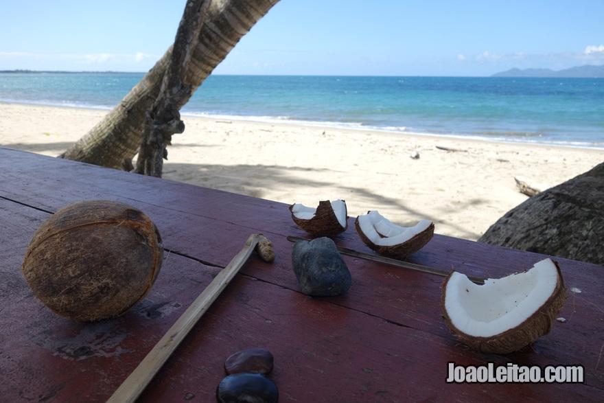 Arranjar ferramentas para abrir cocos na praia