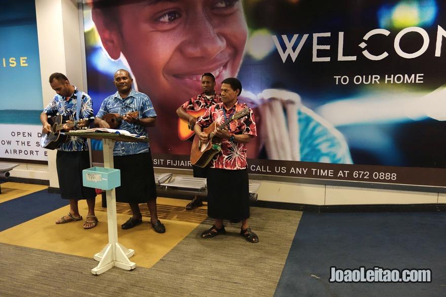 Ser recebido por músicos no aeroporto de Nadi para desejar boas vindas