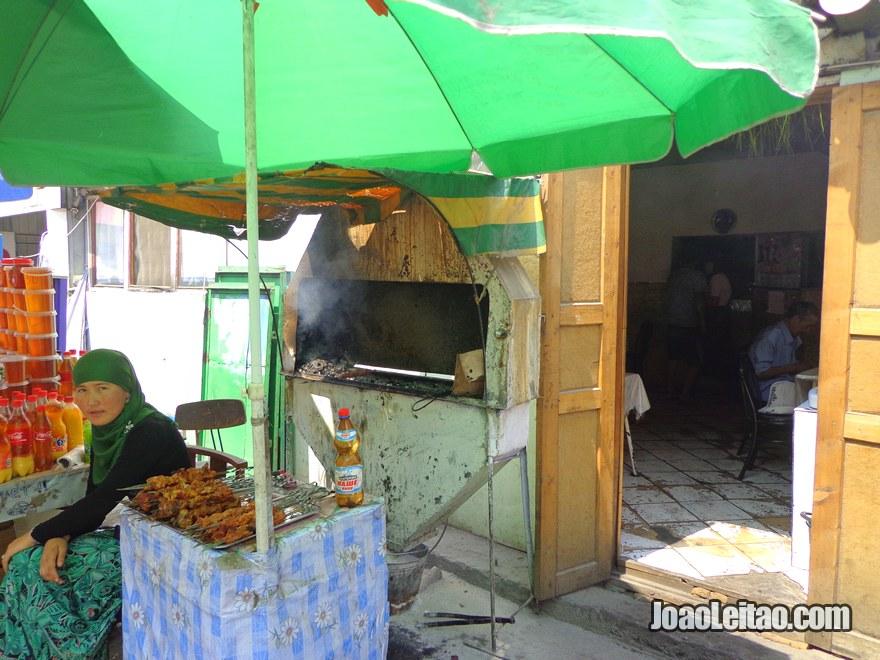 Senhora a grelhar carne num restaurante perto do mercado central