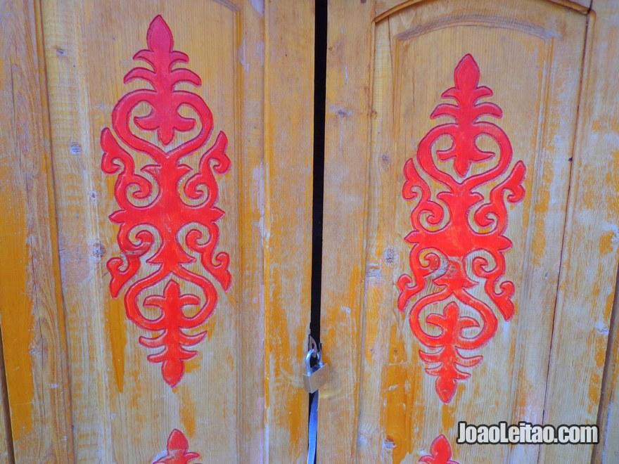 Detalhe de porta de madeira com motivos quirguizes em Bishkek