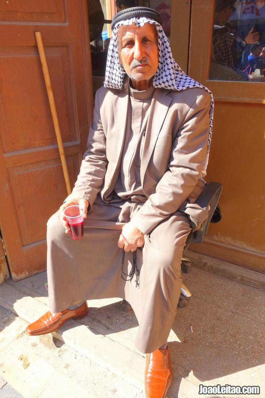 Homem com roupas tradicionais a beber sumo de romã
