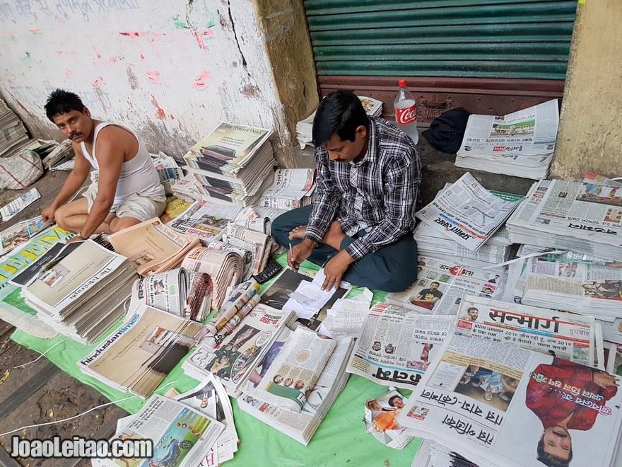 Homens a dobrar jornais na rua em Calcutá