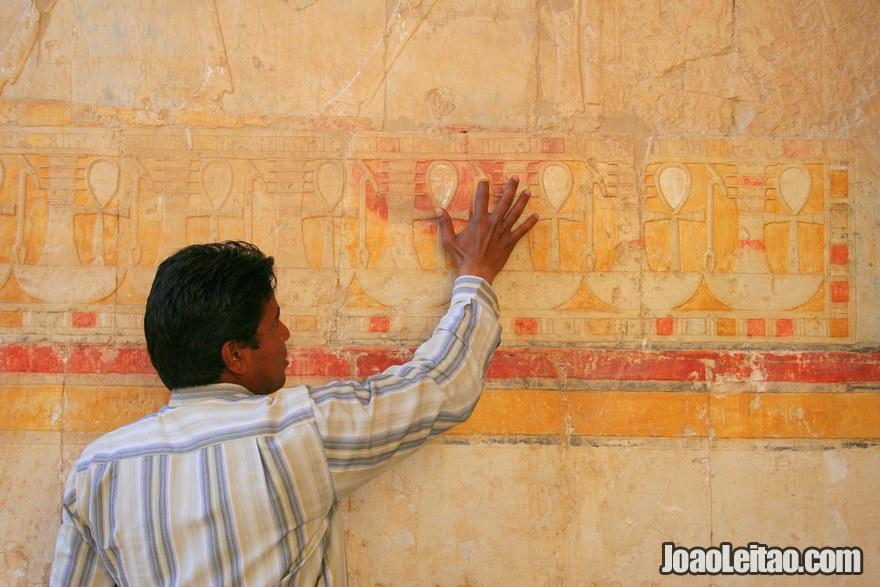 Guia a explicar o significado das figuras e hieróglifos na parede do Templo de Hatshepsut