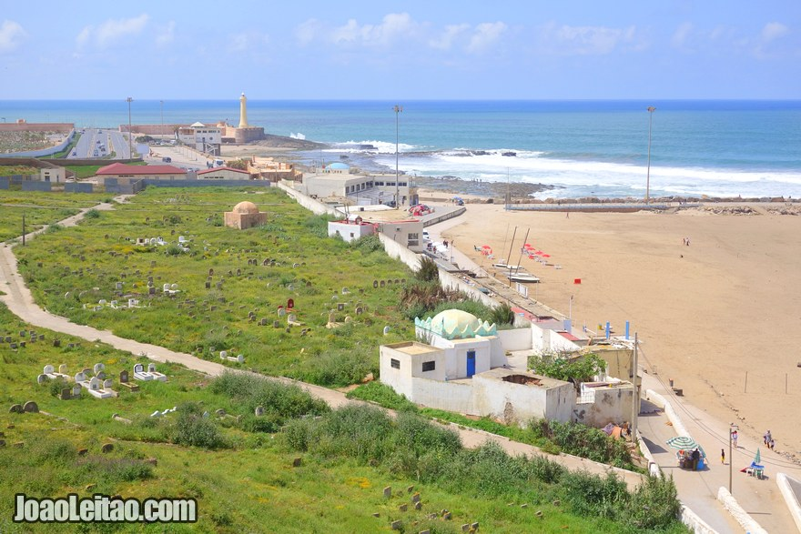 Foto da Praia de Rabat com o cemitério do lado esquerdo e o farol ao fundo