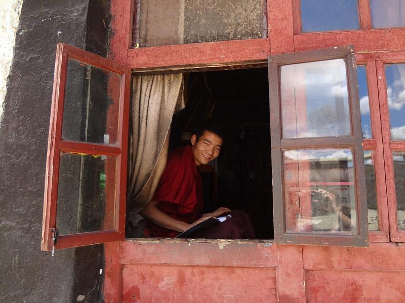 Um monge tibetano à entrada do Mosteiro Tashilhunpo