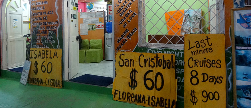 Last Minute cruises departure prices outside an agency in Puerto Ayora