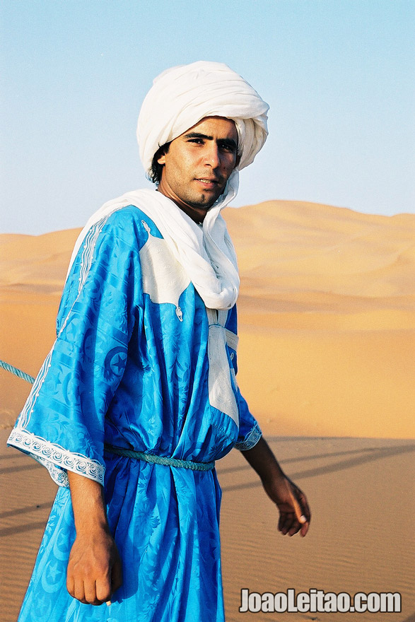 Young man crossing the Erg Chebbi Dunes in Sahara Desert, Morocco