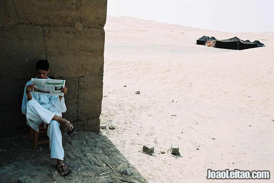 Photo of boy reading the newspaper in Sahara Desert, Morocco