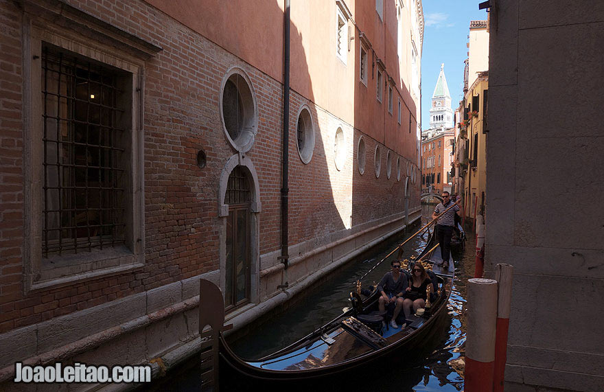 Venice narrow canal with tourist on a gondola ride
