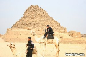 Police officers riding camels
